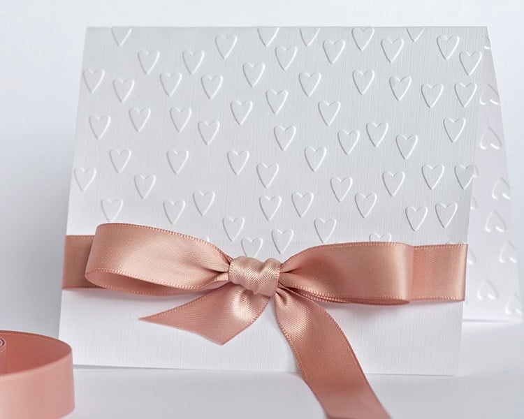 handmade card with embossed hearts and beige bow on white backgr